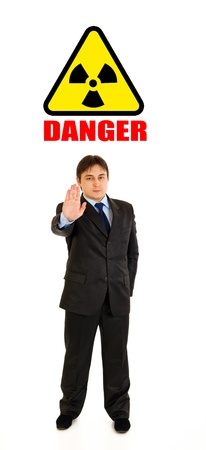 Сoncept-radiation hazard! Full length portrait of confident businessman showing stop gesture isolated on white  photo