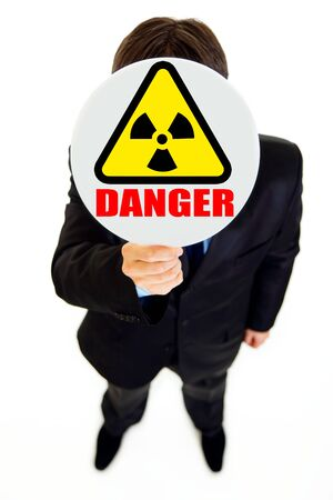Сoncept-radiation danger! Businessman holding radiation sign in front of face isolated on white