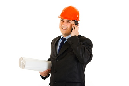 Smiling businessman in helmet holding building plans and talking on mobile isolated on white  photo