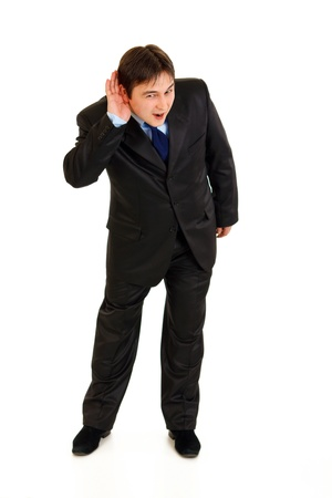 stressful: Full length portrait of stressful businessman holding hand at ear and listening isolated on white  Stock Photo