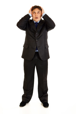 Full length portrait of shocked businessman holding hands near head and looking up isolated on white Stock Photo - 9515477