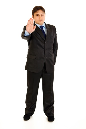 certitude: Full length portrait of confident  modern businessman showing stop gesture isolated on white
