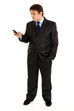 Full length portrait of businessman holding mobile in hand and looking on it isolated on white  photo