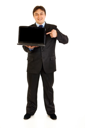 Full length portrait of smiling modern businessman pointing finger on laptops blank screen isolated on white  photo