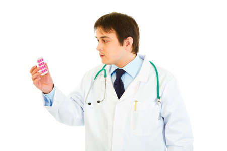 centrality: Concentrated medical doctor looking on pills pack isolated on white  Stock Photo