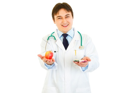 Smiling medical doctor with pills in one hand and apple in other isolated on white