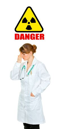 Concept-radiation hazard! Tired medical doctor woman holding hand near forehead isolated on white Stock Photo - 9515513