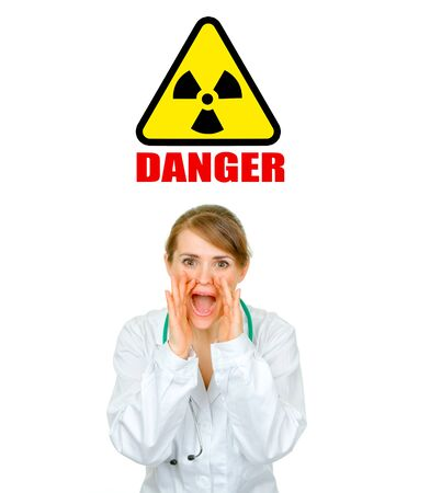 Concept- radiation danger! Medical doctor woman shouting through megaphone shaped  hands isolated on white