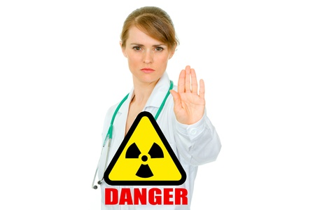 Concept- radiation danger! Strict medical female doctor showing stop gesture isolated on white Stock Photo - 9515390