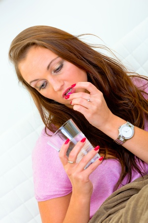Sick young woman taking pill and holding glass of water  photo
