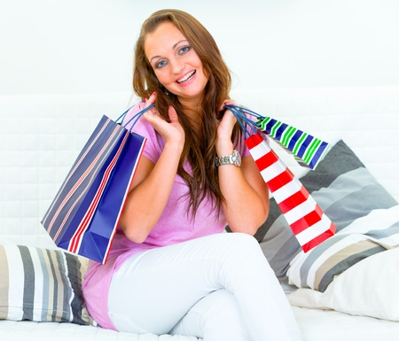 Happy pretty woman sitting on couch at home and holding shopping bags in hands  photo