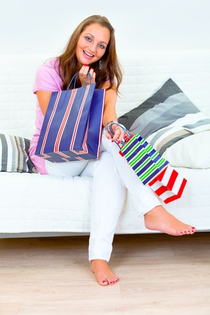 Laughing pretty woman sitting on divan at home and holding shopping bags in hands  photo