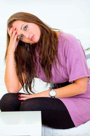 Sad young woman sitting on white couch at home Stock Photo - 9558042