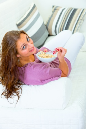 Smiling young woman sitting on sofa at home and eating muesli  photo