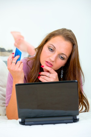 Lying on sofa at home pensive woman using credit card for internet shopping  photo