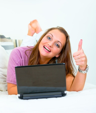 Smiling pretty woman lying on sofa at home with laptop and showing thumbs up gesture  photo