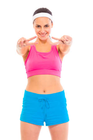 Smiling confident young  girl in sportswear showing victory gesture isolated on white