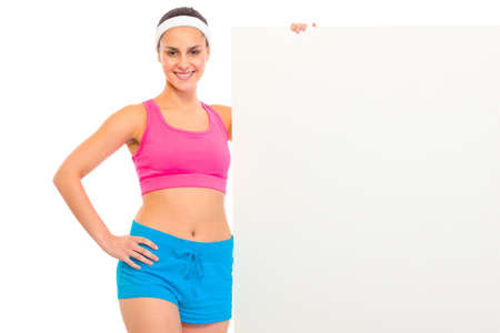 Smiling fitness young girl in sportswear holding blank billboard isolated on white