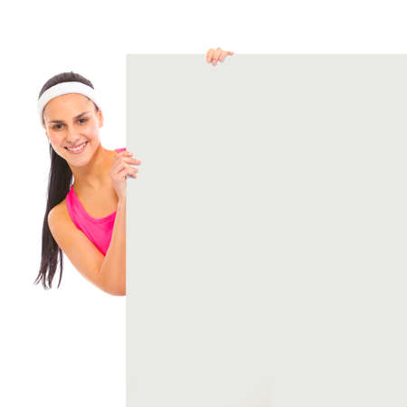 Smiling young girl looking out from blank billboard isolated on white Stock Photo - 9616995