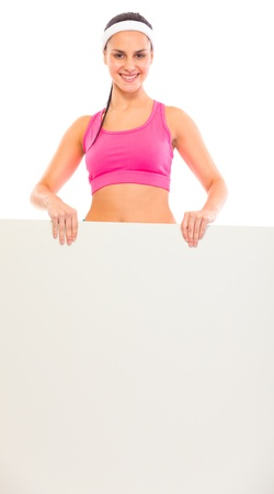 Smiling young fit girl holding blank billboard in hands isolated on white