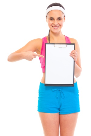 ragazza che indica: Smiling young fit girl pointing finger at blank clipboard isolated on white