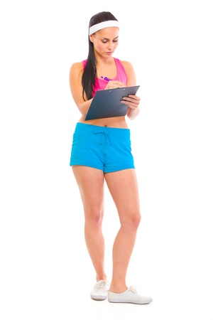 making notes: Serious young fitness trainer making notes in training plan isolated on white