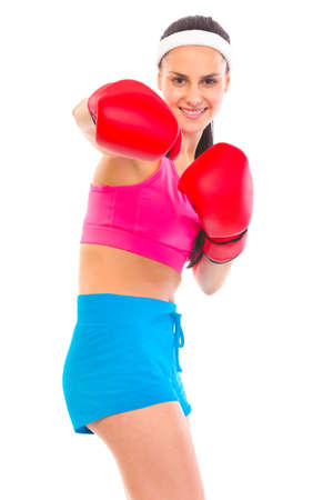 Cheerful fit young girl in boxing gloves punching isolated on white  photo