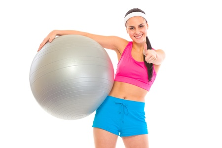 Smiling fit young girl with fitness ball showing thumbs up gesture isolated on white Stock Photo - 9615422