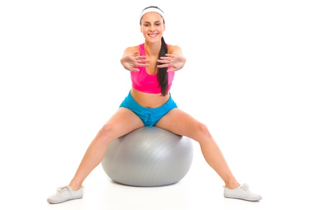 Smiling young girl doing exercises on fitness ball isolated on white  photo