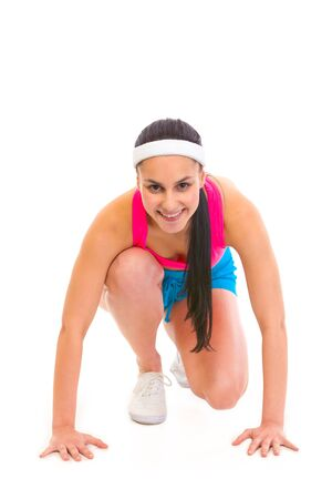 start position: Smiling fitness young girl in start position ready for race isolated on white  Stock Photo