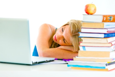 Tired young girl sleeping on table with books and laptop  photo