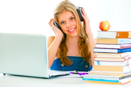 Sitting at table smiling teengirl with headphone listening audio lessons  photo