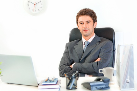 Smiling modern business man with crossed arms on chest sitting at office desk  photo
