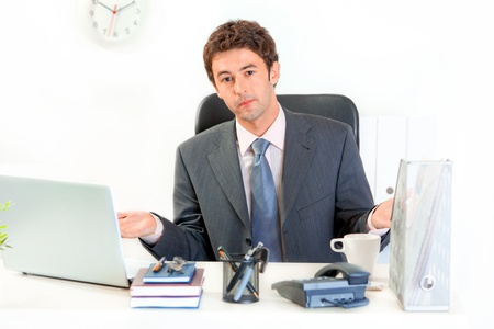 dismay: Confused modern business man sitting at office desk  Stock Photo