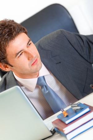 Alert modern business man sitting at office desk  and looking in corner. Close-up  photo