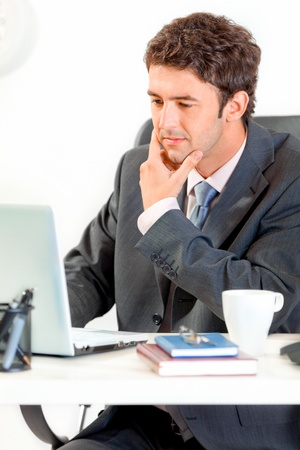 Thoughtful modern businessman sitting at office desk and working on laptop  photo