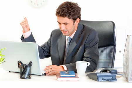 brandishing: Angry modern businessman sitting at office desk and menacingly brandishing his fist on laptop