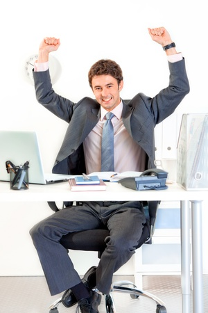 Excited modern businessman sitting at office desk and rejoicing his success   photo