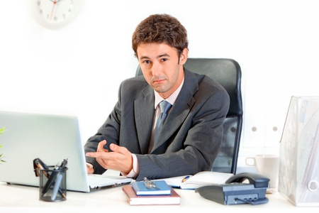 Modern business man sitting at office desk and pointing finger on laptop  photo