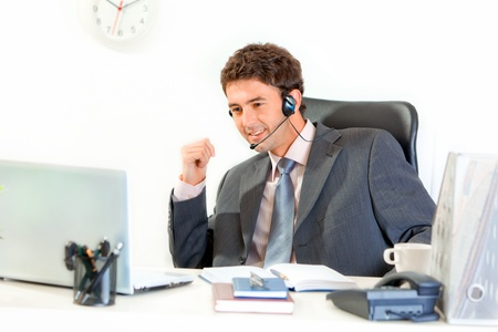 handsfree phone: Smiling modern businessman with  headset sitting at office desk and looking  on laptop  Stock Photo