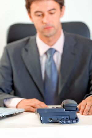 businessman waiting call: Modern businessman sitting at office desk and expecting phone call. Focus on phone