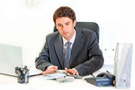 Modern business man  sitting at office desk and giving money packs  photo