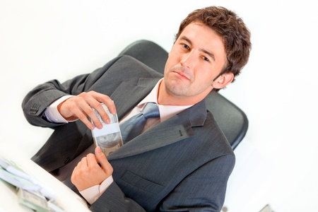 putting money in pocket: Confident modern businessman sitting at office desk and putting money in pocket