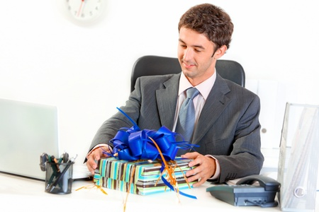 copyspace corporate: Pleased modern businessman sitting at office desk and looking on gift