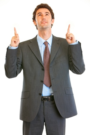 interrogatively: Interested modern businessman pointing finger up at copy space isolated on white