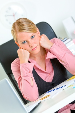 tedium: Bored modern business woman sitting at office desk and keep head on hands  Stock Photo