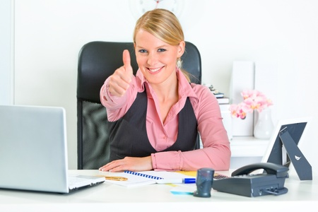 business woman phone: Smiling modern business woman sitting at office desk and  showing thumbs up gesture  Stock Photo