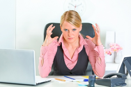 Angry modern business woman sitting at office desk and holding hands near head