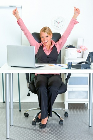 Excited modern business woman sitting at office desk and rejoicing her success   photo