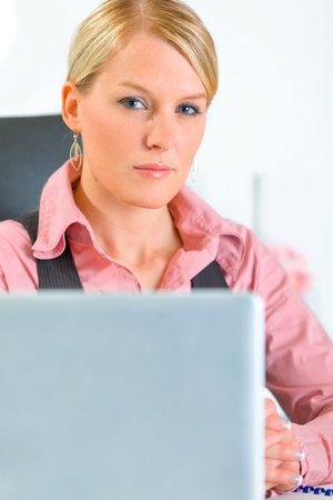 Confident modern business woman sitting at office desk. Close-up  photo